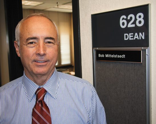 man with red tie standing in front of Dean's office