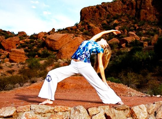 Woman doing yoga pose on red rock